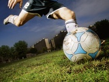 Soccer Player Kicking Ball Fotografisk tryk af Randy Faris