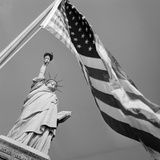 View of Statue of Liberty and American Flag Photographic Print by  Bettmann