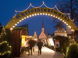 Sign Over Gate and Stalls, Christmas Market (Christkindlmarkt) on Kapellplatz Square, Bavaria Photographic Print by Richard Nebesky