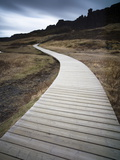 Boardwalk Meandering Towards Cliffs and Stormy Sky at Thingvellir National Park Near Reykjavik Photographic Print