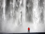 Man in Red Jacket Standing in Front of the Skogafoss Waterfall Near the Village of Skogar, Iceland Photographic Print by Lee Frost