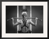 Rear View of a Woman Exercising on a Machine Framed Photographic Print