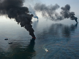 Smoke rises from surface oil being burned by cleanup crews. Photographic Print by Joel Sartore