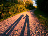 The Long Shadow of a Couple Holding Hands Cast on a Dirt Road Photographie par Amy & Al White & Petteway
