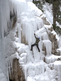 An Ice Climber Climbing with an Ice Axe on a Frozen Waterfall Fotografisk tryk af Robbie George