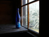 A Blue, Spider Web-Draped Wine Bottle Sitting in a Window Photographic Print by Amy & Al White & Petteway