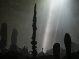 Streams of Light Unveil Stalagmites on the Floor of Hang Loong Con Photographic Print by Carsten Peter