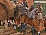 An Elephant Orphan Greets Schoolchildren Visiting Tsavo National Park Fotodruck von Michael Nichols