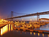 Boats on the River Tagus Move at Night in the Doca De Santa Amaro Marina under the 25 April Bridge, Photographic Print by Stuart Forster