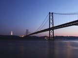 The 25 April Suspension Bridge at Dusk over the River Tagus (Rio Tejo), Christus Rei Is Illuminated Photographic Print by Stuart Forster