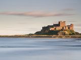 Bamburgh Castle Bathed in Golden Evening Light Overlooking Bamburgh Bay with the Sea Filling the Fo Photographic Print by Lee Frost