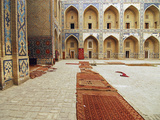 Arched Entrance in a Row of Historic Building with Carpets Lying on Courtyard, Bukhara, Uzbekistan Photographic Print by Anthony Asael
