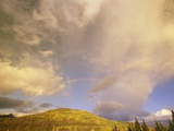 A Rainbow Shows Through Cumulus Clouds over the Mackenzie River Valley Photographic Print by John Eastcott & Yva Momatiuk