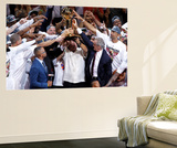 Miami, FL - June 21:  Team owner Micky Arison of the Miami Heat holds up the Larry O'Brien Champion Wall Mural by Mike Ehrmann