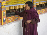 A Woman, Prayer Beads in Hand Spins Brass Prayer Wheels as She Mutters Invocation to Protective Dei Photographic Print by Nigel Pavitt