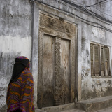 Zanzibar, Tanzania. a Zanzibari Women in Traditional Khanga Robes, Passing an Old Wooden Door in St Photographic Print by Steve Outram