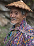 A Wizened Old Farmer Near Mongar Wears the Traditional Knee-Length National Robe Called Gho and a B Photographic Print by Nigel Pavitt