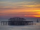 Storbritannien, England, Sussex, Brighton, et skib sejler forbi resterne af Vestmolen i Brighton ved solnedgang Fotografisk tryk af Jane Sweeney