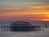 Jane Sweeney - UK, England, Sussex, Brighton, Boat Sailing Past Remains of Brighton West Pier at Sunset - Fotografik Baskı