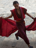 A Young Monk Holds His Red Robes and Runs across Wangdue Phodrang Dzong (Fortress) Courtyard, Massi Photographic Print by Nigel Pavitt
