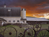 A Fence of Wagonwheels and Large Gears in Front of a Large Barn at Dusk, Washington, USA Photographic Print by Sean Bagshaw
