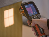 A Thermal Imaging Camera Being Used to Demonstrate Heat Loss from Building Windows Photographic Print by Ashley Cooper
