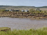 Tourists in Safari Vehicles Witnessing Wildebeest Migration across Mara River Photographic Print by Adam Jones