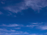 Cirrus Clouds in a Clear Blue Sky Photographic Print by Michael Johnson