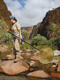 An Entomologist with a Collecting Net on a Wadi in Socotra, Yemen Photographic Print by Fabio Pupin