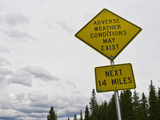 A Road Sign Warns of Adverse Weather Conditions Along the Continental Divide Fotografie-Druck von Jon Van de Grift