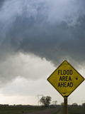 A Road Sign Warns of Flooding on a Rural Road in Kansas as a Tornadic Thunderstorm Spins Above Photographic Print by Jon Van de Grift