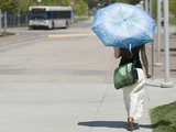 A Woman Wears Loose Fitting Clothing and Carries an Umbrella to Block the Sun During Heat Wave Fotografie-Druck von Jon Van de Grift