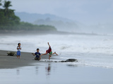 Kids Playing on the Beach While Olive Ridley Sea Turtle Come Ashore Photographic Print by Solvin Zankl