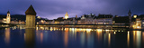 Buildings Lit Up at Dusk, Chapel Bridge, Reuss River, Lucerne, Switzerland Photographic Print by  Panoramic Images