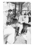 Enrico Caruso Leans Back on Chair Holding a Board with Music Posters