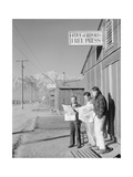 Roy Takeno (Editor) and Group Reading Manzanar Paper [I.E. Los Angeles Times] in Front of Office Art by Ansel Adams