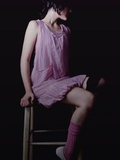 A Young Woman Wearing a Short Purple Dress Sitting on a Stool Photographic Print by Martina Zancan