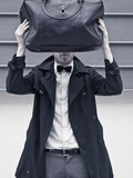 A Man Wearing a Bow Tie Hiding Behind a Bag Photographic Print by India Hobson