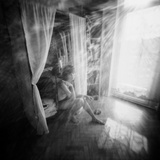 A Young Woman Smoking a Cigarette Seated in the Sunlight Shining through a Window Photographic Print by Rafal Bednarz
