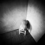 A Naked Female Figure Sitting on a Stool in the Corner of an Empty Room Photographic Print by Rafal Bednarz