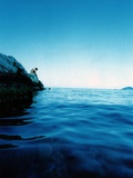 A Figure Sitting on Rocks by a Blue Sea Photographic Print by Jason Martin