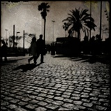 Silhouettes of Two People Walking on a Cobbled Street with Palm Trees Photographic Print by Eudald Castells
