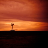 A Wind Pump Set Against an Orange Sky Photographic Print by Mark James Gaylard