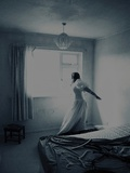 A Young Girl Wearing a Long White Dress Standing in a Bedroom Near a Window Photographic Print by India Hobson