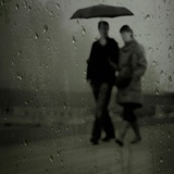 Two Young People Walking in the Rain Holding an Umbrella Photographic Print by Eudald Castells
