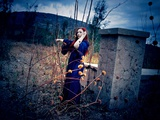 A Young Woman with Red Hair Wearing a Long Blue Gown, Standing Outside Pointing to a Garden Photographic Print by Elizabeth May