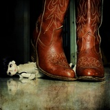 A Pair of Cowgirl Boots over a Little Doll Photographic Print by Kimberley Ross