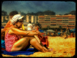 An Old Woman Wearing a Bathing Costume and White Hat Sitting on a Beach with Hotels Photographic Print by Cristina Carra Caso