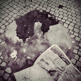 An Old Church Reflected in a Puddle with an Old Newspaper Photographic Print by Kimberley Ross