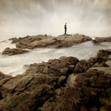 A Lone Man Standing on Large Rocks with the Seas Swirling around Them Impressão fotográfica por Luis Beltran
